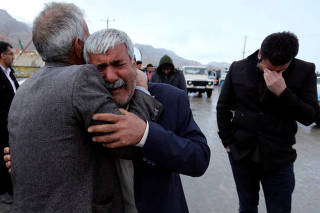 Relatives of passengers who were believed to have been killed in a plane crash react near the town of Semirom