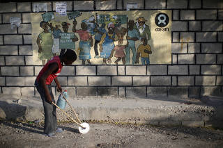 A boy playing with a homemade toy walks past an Oxfam sign in Corail, a camp for displaced people of the earthquake of 2010, on the outskirts of Port-au-Prince