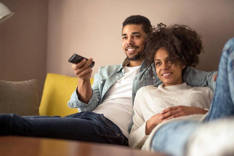 Casal sentado no sofá assistindo a televisão