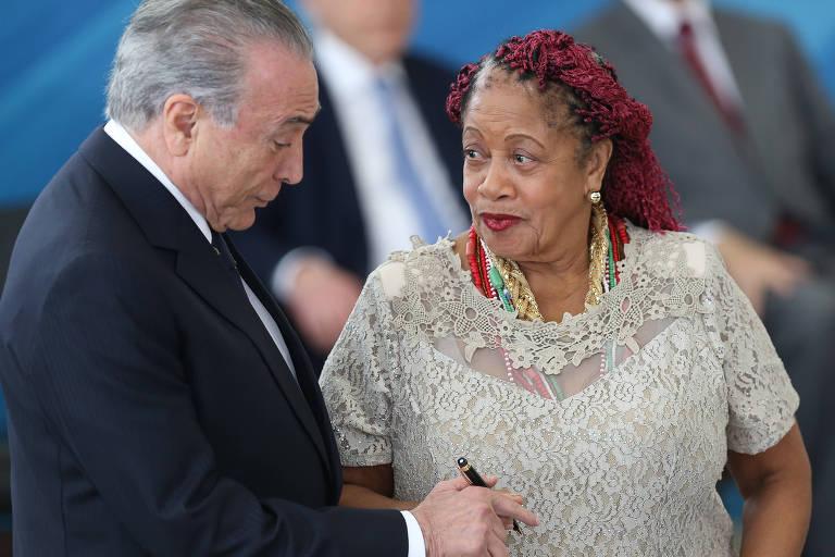 O presidente Michel Temer assina o termo de posse da ministra Luislinda Valois, ao seu lado, em cerimônia em fevereiro de 2017, no Planalto