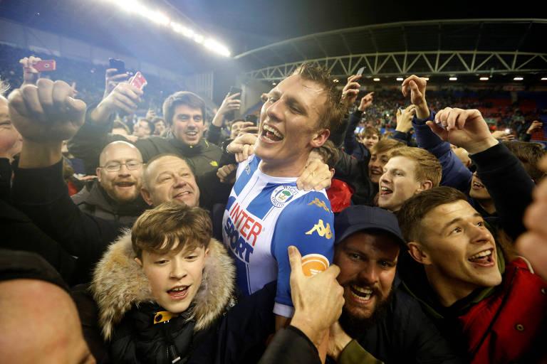 Torcedores do Wigan Athletic invadem o campo para comemorar com os jogadores a vitória que eliminou o Manchester City da Copa da Inglaterra