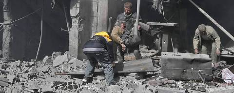 Syrian men carry an injured victim amid the rubble of buildings following government bombing in the rebel-held town of Hamouria, in the besieged Eastern Ghouta region on the outskirts of the capital Damascus, on February 19, 2018. Heavy Syrian bombardment killed 44 civilians in rebel-held Eastern Ghouta, as regime forces appeared to prepare for an imminent ground assault. / AFP PHOTO / ABDULMONAM EASSA