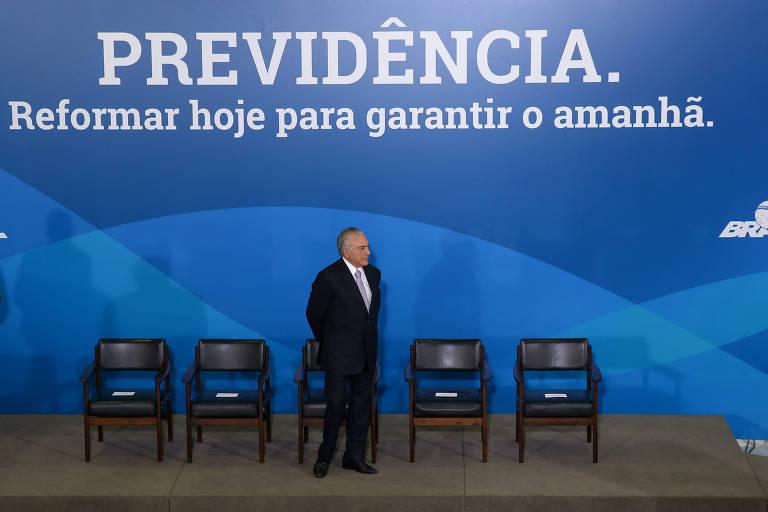 """O presidente Michel Temer no palco com cadeiras e ao fundo o cartaz """"Previdência. Reformar hoje para garantir o amanhã"""""""