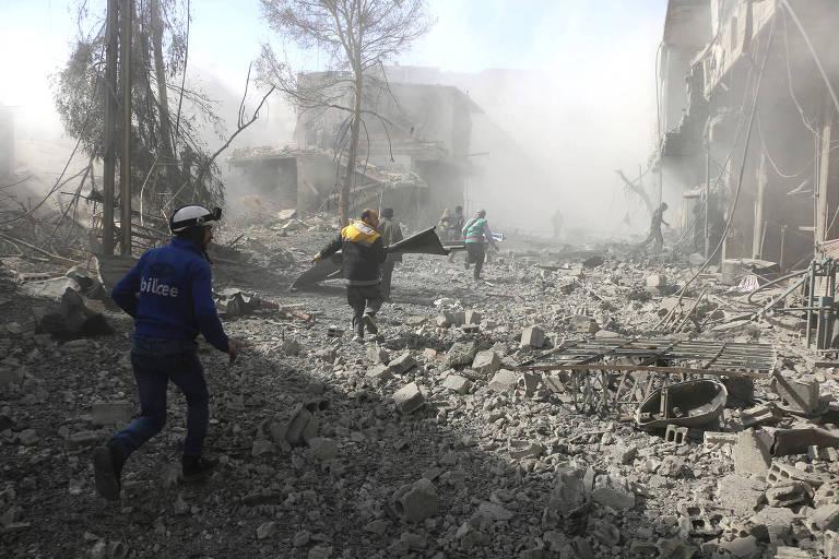 Integrantes dos White Helmets ajudam sobreviventes a deixarem uma rua de Ghouta após um bombardeio região após um bombardeio