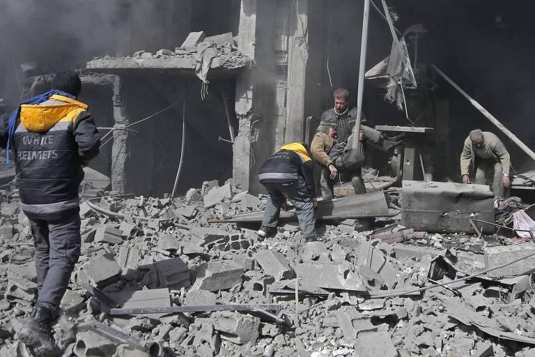 Um homem carrega uma criança enquanto outro busca sobrevivente em destroços em Ghouta Oriental