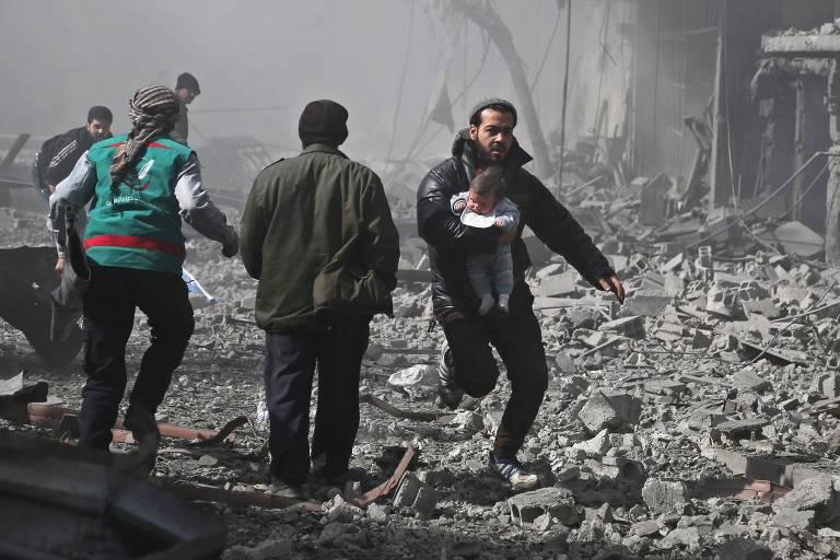Moradores da cidade de Hamouria, em Ghouta Oriental, deixam o local após um bombardeio