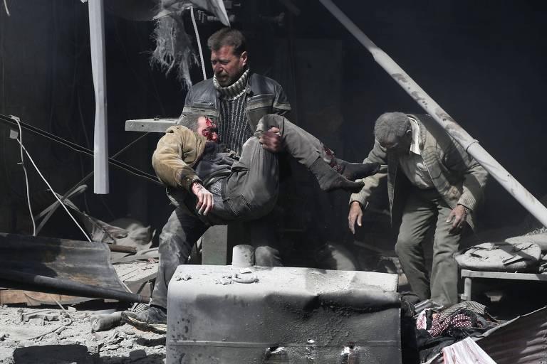 Homem carrega uma pessoa ferida após o ataque em Hamouria; região é último posto rebelde próximo da capital Damasco