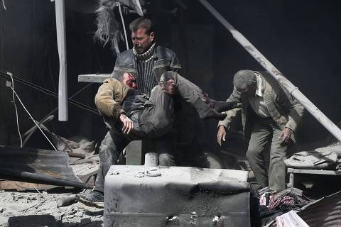 A Syrian man carries an injured victim amid the rubble of buildings following government bombing in the rebel-held town of Hamouria, in the besieged Eastern Ghouta region on the outskirts of the capital Damascus, on February 19, 2018. Heavy Syrian bombardment killed 44 civilians in rebel-held Eastern Ghouta, as regime forces appeared to prepare for an imminent ground assault. / AFP PHOTO / ABDULMONAM EASSA