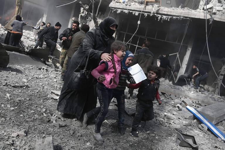 Mulher síria ajuda crianças após ataque em Hamouria; mais de cem pessoas já morreram na região após o início dos ataques