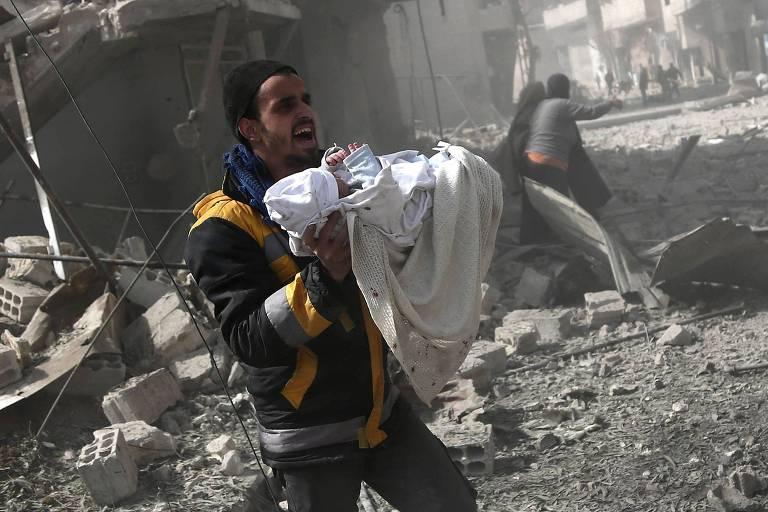 Homem carrega um bebê ferido nos ataques contra Hamouria, em Ghouta Oriental