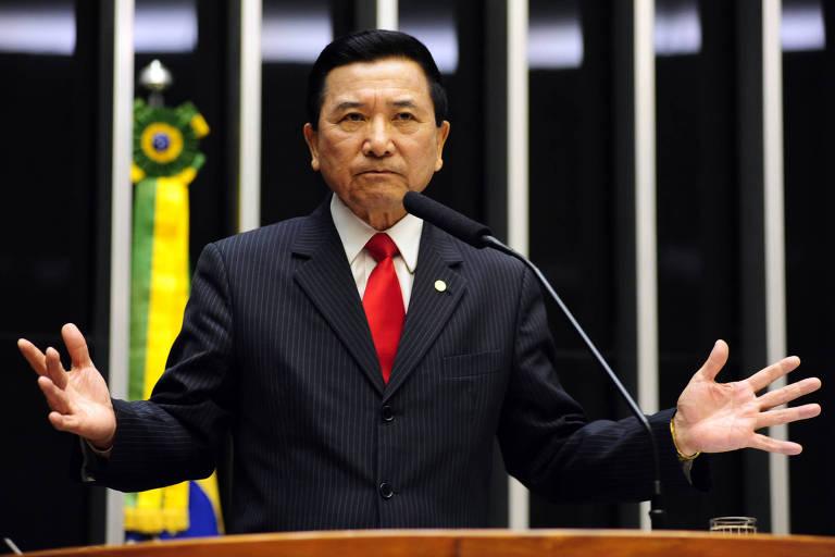 O deputado Junji Abe discursa no plenário da Câmara dos Deputados. Ele usa terno e gravata vermelha. Ao fundo, aparece uma faixa com as cores da bandeira do Brasil.
