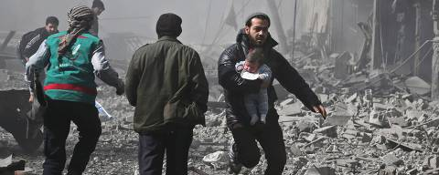 A Syrian man carries an infant injured in government bombing in the rebel-held town of Hamouria, in the besieged Eastern Ghouta region on the outskirts of the capital Damascus, on February 19, 2018.