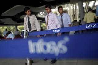 FILE PHOTO: File photo of employees of Indian software company Infosys walking past Infosys logos at their campus in the Electronic City area in Bangalore