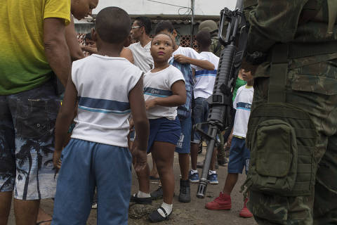A young student looks at a Brazilian marine as she and her classmates have their bags inspected during a surprise operation in Kelson's slum in Rio de Janeiro, Brazil, Tuesday, Feb. 20, 2018. Members of the armed forces and the police spread out in the slum in northern Rio in the first major operation since the military took control of security forces in the state. (AP Photo/Leo Correa) ORG XMIT: XLC105