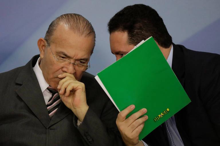 Dyogo Oliveira (Planejamento) usa pasta para cobrir o rosto e cochichar com Eliseu Padilha