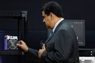 Venezuela's President Nicolas Maduro examines a cryptocurrency mining computer during the event launching the new Venezuelan cryptocurrency
