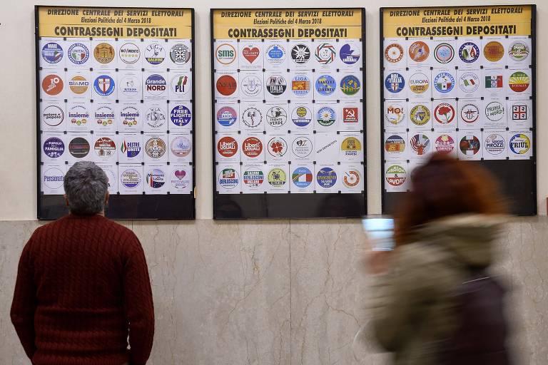 Eleitores observam as marcas dos partidos autorizados a concorrerem nas eleições legislativas da Itália, em 4 de março