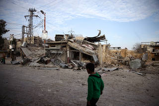 A child walks near damaged buildings in the besieged town of Douma