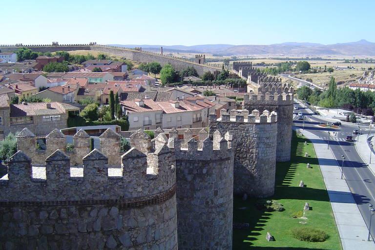 A muralha de Ávila tem torres redondas por toda a sua extensão. Na foto, fica clara a divisão entre a cidade, no lado esquerdo, com o exterior, no direito, onde somente há uma rua pavimentada