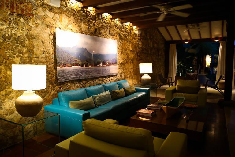 A sala da Casa Turquesa tem paredes de tijolos com pouco ou nenhum revestimento. Há vigas de madeira no teto. Na parede, uma foto do mar e da serra, e abaixo um sofá turquesa de quatro lugares, rodeado por duas poltronas e abajures