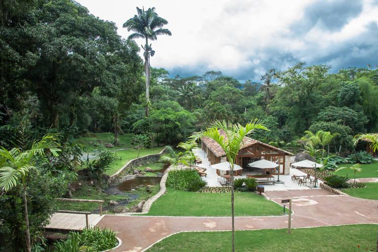 A casa do restaurante da fazenda Bananal fica abaixo de uma colina, de onde foi tirada a foto. Ele tem aparência rústica, de madeira. Ao redor, um amplo espaço de grama, que chega até uma floresta que cerca a área
