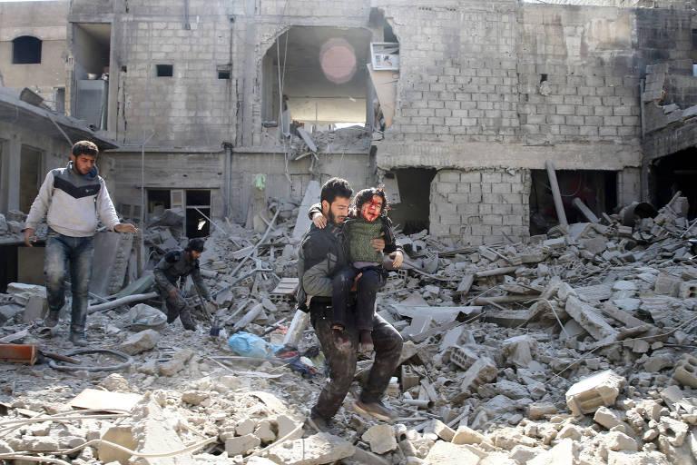 Homem carrega menino ferido após bombardeio em Ghouta nesta quarta (21)