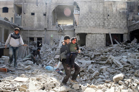 ATTENTION EDITORS - VISUAL COVERAGE OF SCENES OF INJURY OR DEATH A man carries an injured boy as he walks on rubble of damaged buildings in the rebel held besieged town of Hamouriyeh, eastern Ghouta, near Damascus, Syria, February 21, 2018. REUTERS/Bassam Khabieh TEMPLATE OUT ORG XMIT: GGGSYR02