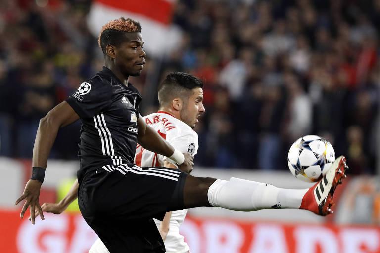 O francês Paul Pogba, do Manchester United, disputa a bola com Pablo Sarabia, do Sevilla, em jogo válido pela Liga dos Campeões
