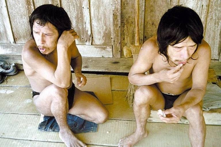 Dois homens de cabelos longos e escuros estão sentados com vestes que parecem cuecas em um chão de madeira