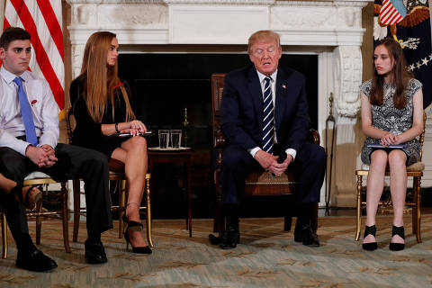 U.S. President Donald Trump, seated with Marjory Stoneman Douglas High School shooting surviving students Jonathan Blank (L), Julia Cordover (2nd L), and Carson Abt (R), delivers remarks during a listening session with Marjory Stoneman Douglas High School shooting survivors and students at the White House in Washington, U.S., February 21, 2018. REUTERS/Jonathan Ernst ORG XMIT: WAS909