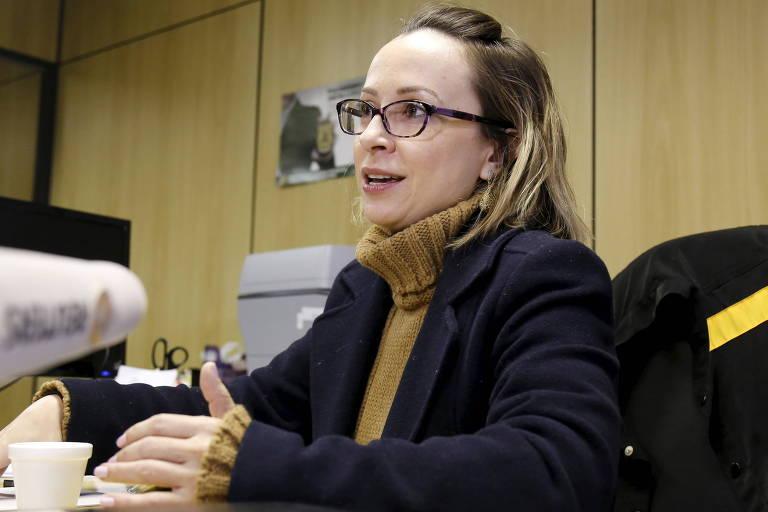 Delegada Erika Marena sentada a sua mesa no gabinete da PF. Ela é loira e usa óculos. Em sua cadeira, um colete com o distintivo da PF está pendurado.