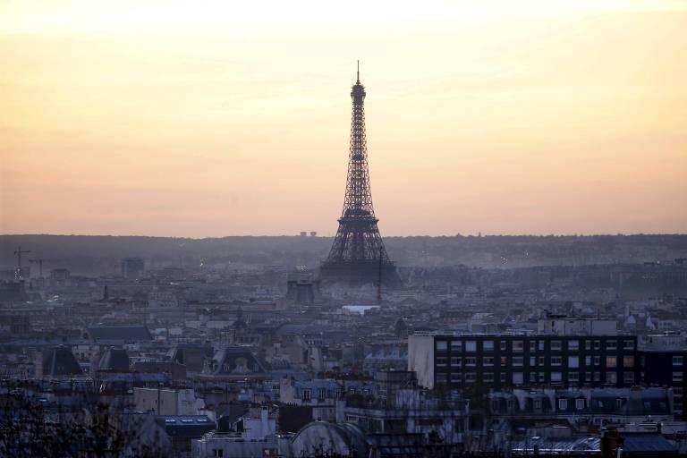A torre Eiffel, símbolo de Paris, é mostrada em destaque no anoitecer da cidade. A foto foi tirada de um ponto alto e mostra todos os prédios a distância. A torre chama a atenção por ser dezenas de metros mais alta do que os prédios na imagem. Pelo horário, o céu tem tons amarelos e alaranjados