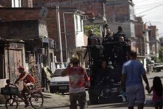 Policemen patrol during an operation at the Mare slums complex in Rio de Janeiro