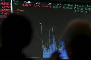People look at the stock quotation board on the floor of Brazil's BM&F Bovespa Stock Market in Sao Paulo