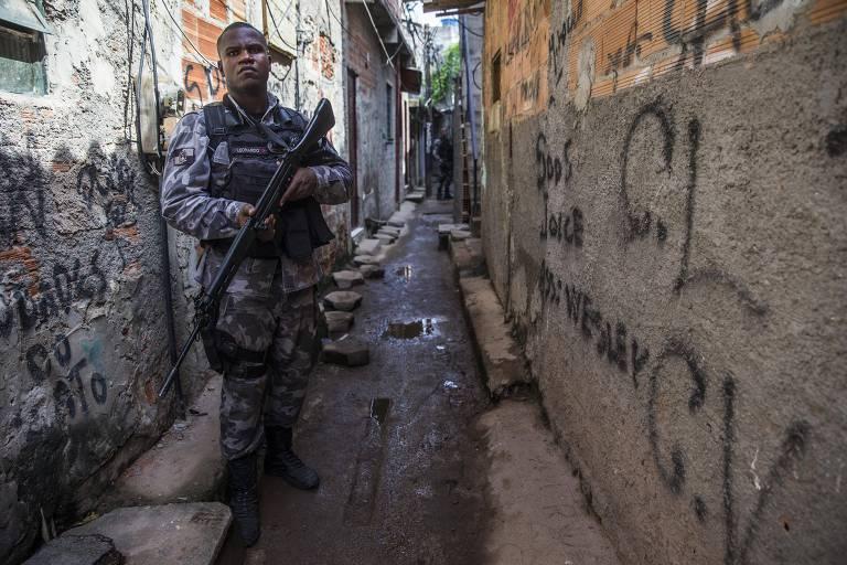 Militar com um fuzil na mão no centro de uma viela com muros pichados