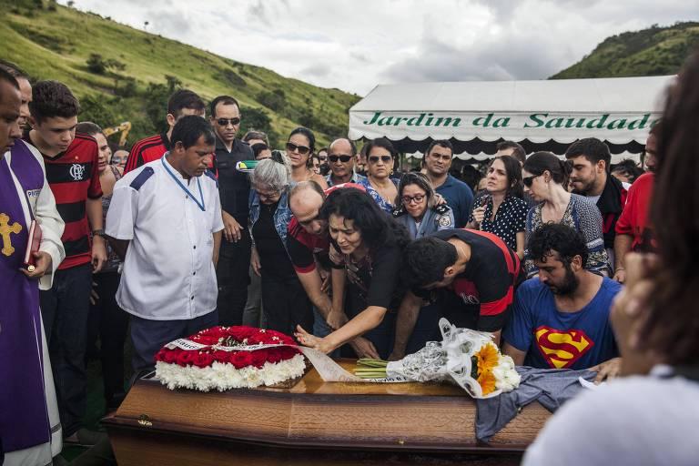 Mulher vestida de preto coloca a mão sobre o caixão do tenente morto no Rio. Várias outras pessoas observam o sepultamento