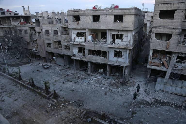 Civis sírios examinam os escombros após o bombardeio do governo na cidade rebelde de Hamouria, na região sitiada de Ghouta Oriental, nos arredores da capital, Damasco