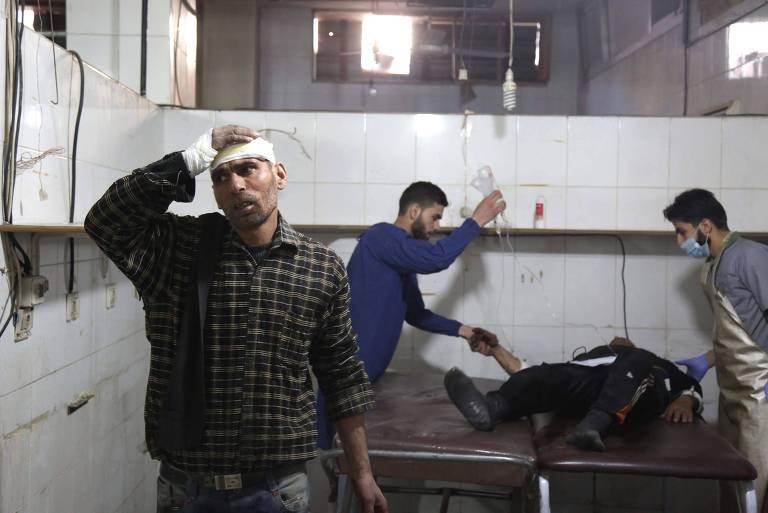 Paramédicos sírios dão assistência médica a uma vítima em um hospital em Kafr Batna após ataques aéreos do governo na cidade de Jisreen, na região sitiada de Ghouta Orienta