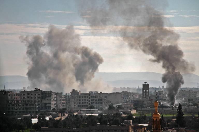 Fumaça sobe dos edifícios após o bombardeamento na aldeia de Mesraba, na região de Ghouta