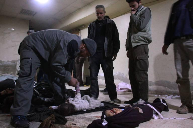 Cadáveres em necrotério em Douma depois de ataques aéreos na aldeia síria de Mesraba, na região sitiada de Ghouta Oriental, nos arredores da capital Damasco