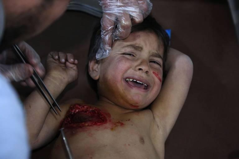 Mohammed chora enquanto recebe tratamento em um hospital em Kafr Batna depois de ter sido ferido com sua mãe em ataques aéreos