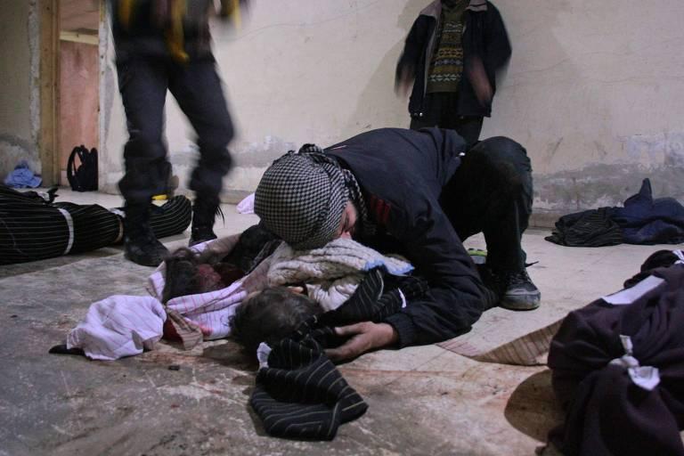 Homem chora sobre seu filho em um necrotério em Douma