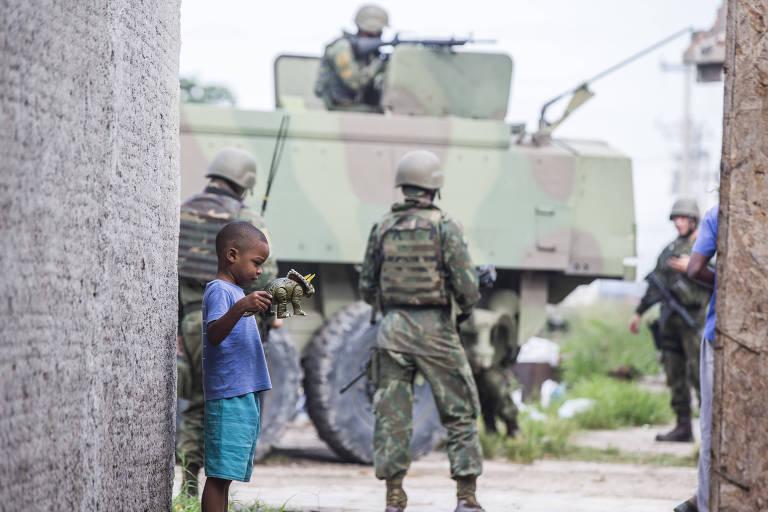 Criança manuseia brinquedo na frente de um tanque de guerra e quatro soldados do Exército