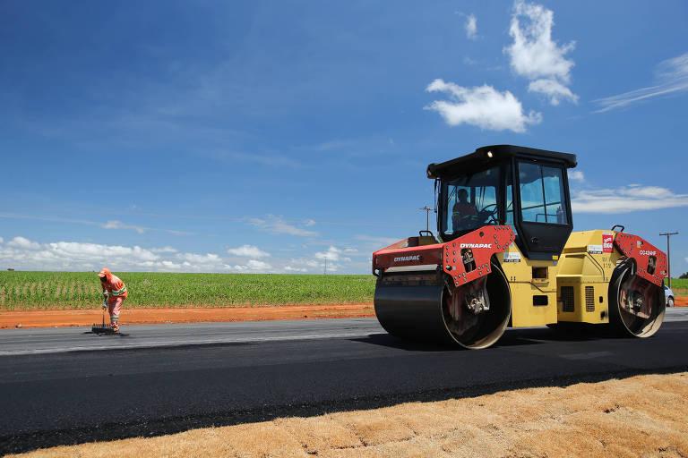 Caminhão recapia asfalta perto de plantação