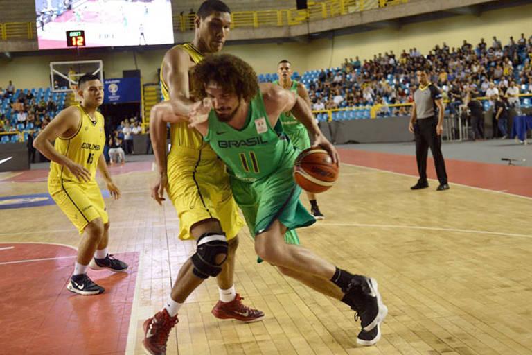 Anderson Varejão tenta passar por um jogador da Colômbia durante partida válida pelas eliminatórias do Mundial de Basquete