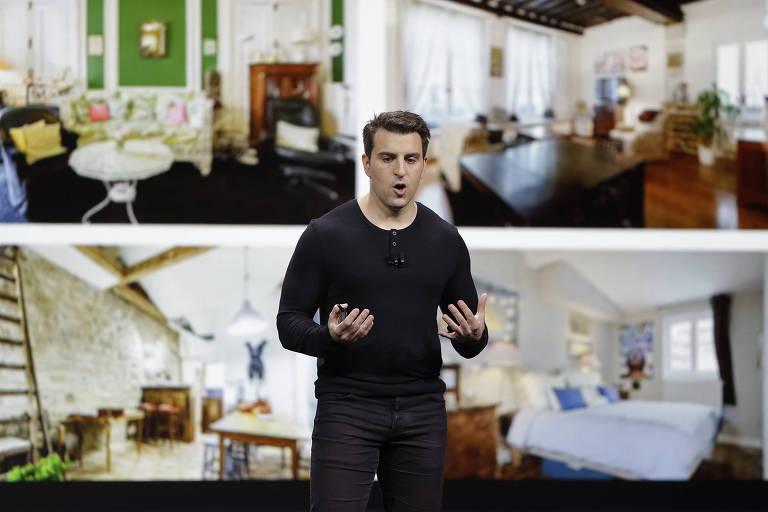O presidente-executivo do Airbnb, Brian Chesky, com imagens de acomodações ao fundo
