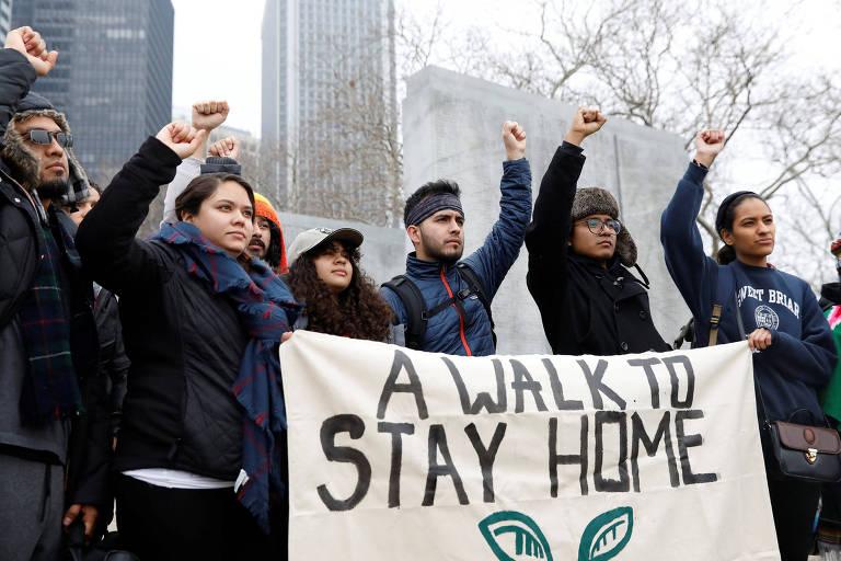 """Grupo de 'sonhadores' erguem faixa onde se vê """"uma caminhada para ficar em casa"""" antes de iniciar os 402 km de caminhada até Washington"""