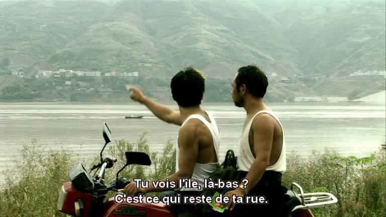 homens em moto apontando para lago