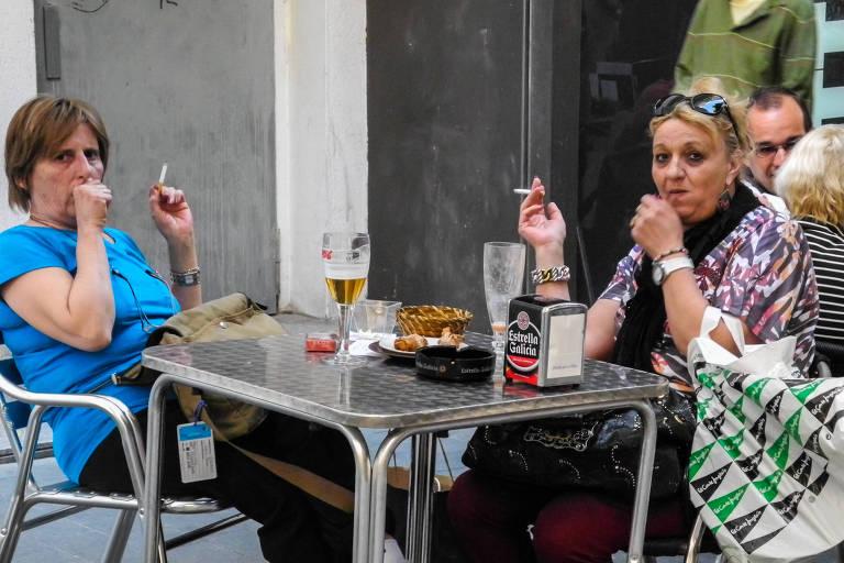 Pessoas com cigarros na mão tossindo
