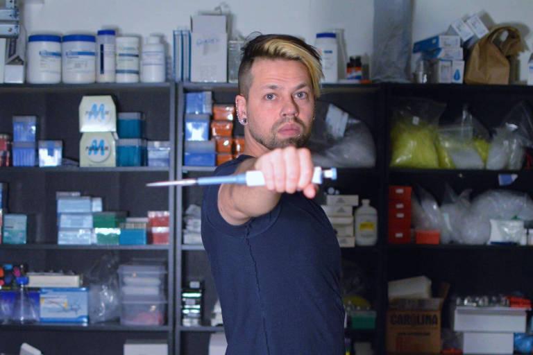 O bioquímico americano Josiah Zayner, 37, segura uma pipeta, um instrumento de laboratório